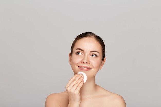 목화 패드와 함께 그녀의 얼굴에서 메이크업을 제거하는 건강 한 신선한 소녀. 회색 벽에 고립 된 면봉 패드로 그녀의 얼굴을 청소하는 아름다움 여자. 피부 관리 및 미용 개념.