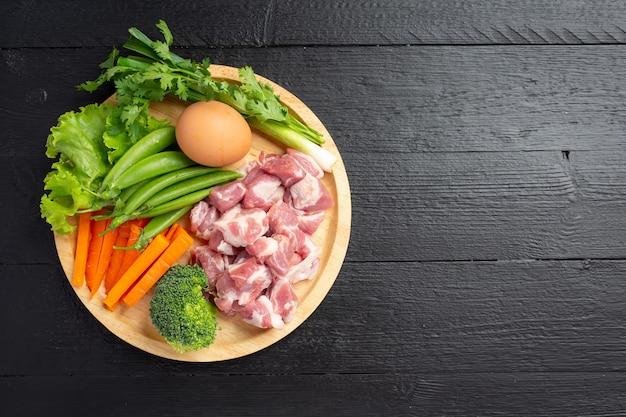 Healthy fresh pet food ingredients on dark surface