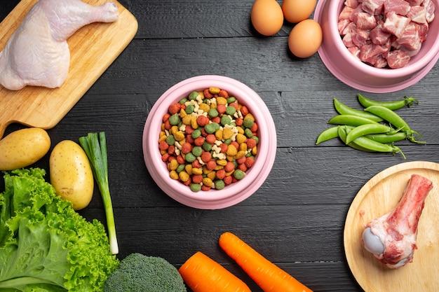 Здоровые свежие ингредиенты корма для домашних животных на темной поверхности