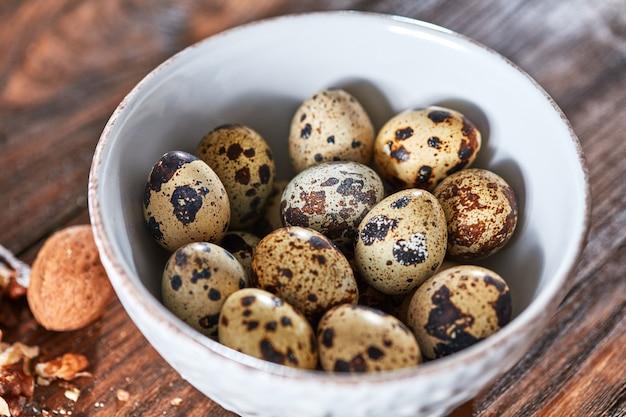 나무 갈색 테이블에 흰색 그릇에 건강 한 신선한 메추라기 달걀