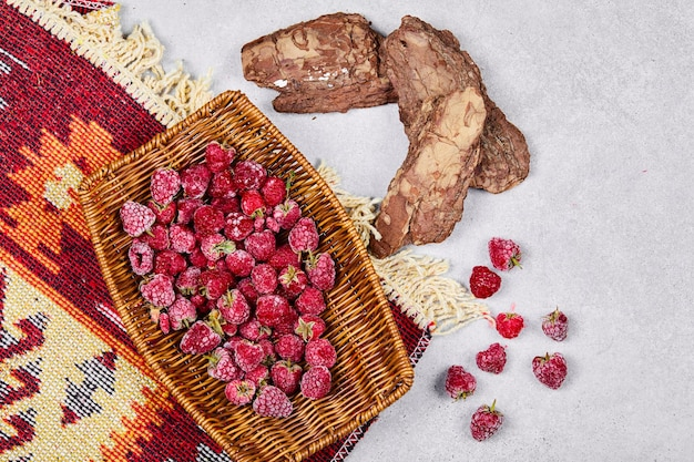 刻まれた敷物と木製のバスケットの健康的な新鮮なラズベリー。