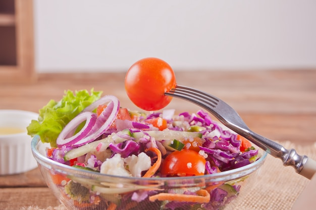 Healthy fresh salad in bowl with red cabbage, tomato, quinoa, green salad and radish