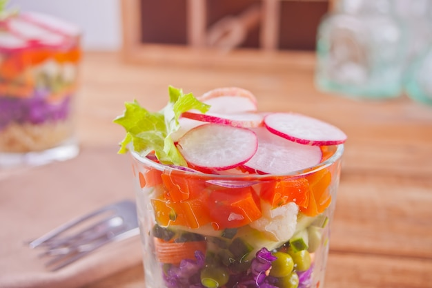 Healthy fresh salad in glassful with red cabbage, tomato, quinoa, green salad and radish on the wooden table