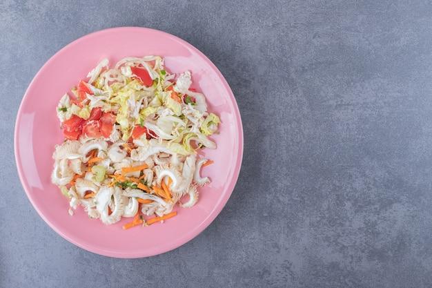 Healthy fresh salad on pink salad.