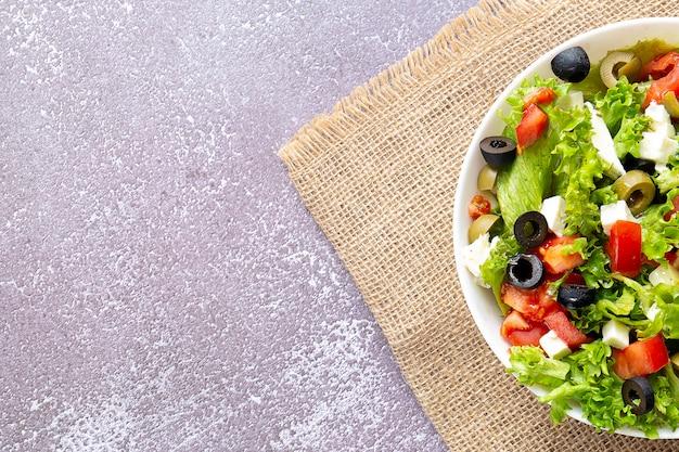 Здоровый свежий салат с листьями салата, оливками, помидорами и сыром фета, копией пространства