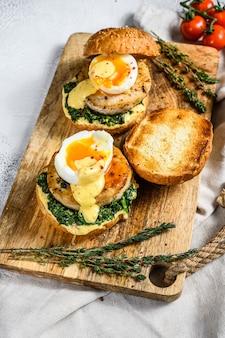 魚の切り身、ほうれん草、卵の健康的な新鮮なシーフードハンバーガー。灰色の背景。上面図