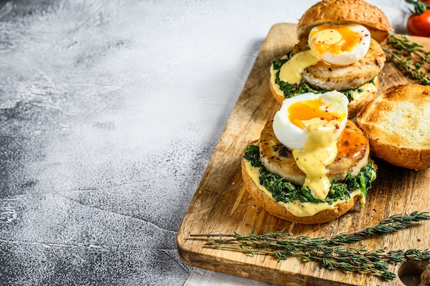 Healthy fresh seafood burger with fish fillet, spinach and egg.  gray surface. top view. copy space