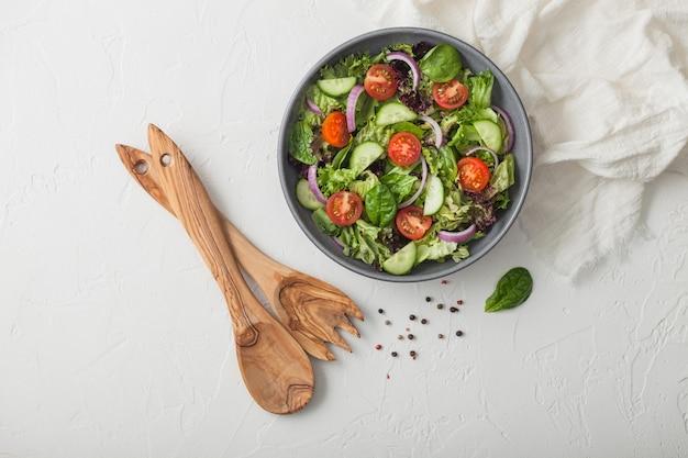 健康的な新鮮なベジタリアン野菜のサラダ、レタスとトマト、赤玉ねぎ、ほうれん草の灰色のボウル