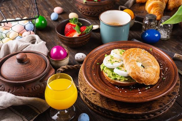 삶은 달걀, 아보카도, 골파로 가득 찬 갓 구운 건강에 좋은 베이글. 아침 식사