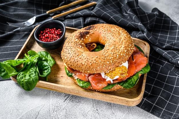 Полезный свежеиспеченный бублик с копченым лососем, шпинатом и яйцом