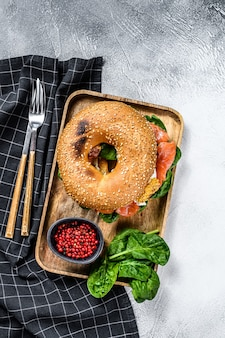 Healthy freshly baked bagel filled with smoked salmon, spinach and egg.  gray surface. top view
