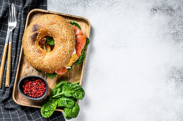 Healthy freshly baked bagel filled with smoked salmon, spinach and egg.