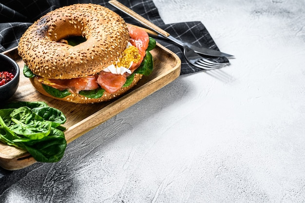 Healthy freshly baked bagel filled with smoked salmon, spinach and egg