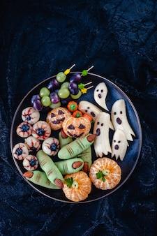 건강한 과일 할로윈 취급합니다. 바나나 유령, 클레멘 타인 오렌지 호박, 열매 눈 및 녹색 마녀 손가락 쿠키