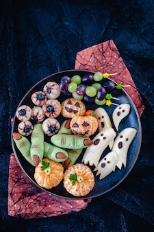 Здоровые фрукты для хэллоуина. банановые привидения, апельсиновые тыквы с клементиной, глазки личи и печенье с зелеными ведьмами