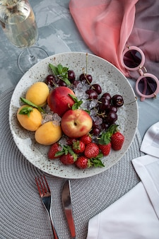 Healthy fruit platter, strawberries, apples, peaches, apricots on a dark gray wooden table, top view, close-up, selective focus.