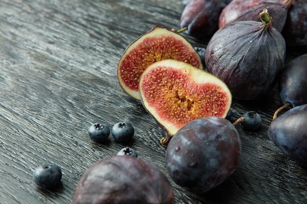 어두운 회색 나무 배경에 건강한 과일과 열매