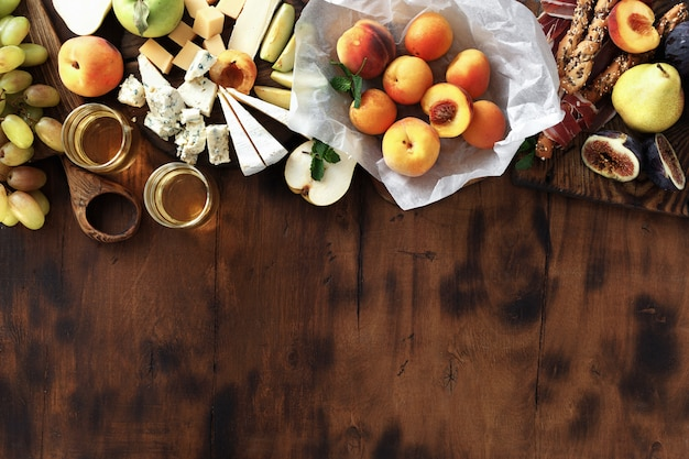 Healthy fruits and cheese on wooden background, top view
