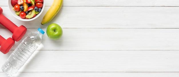 健康的な果物。新鮮なフルーツサラダダイエットスリムフィットダンベルスポーツ用品木製テーブルの背景に
