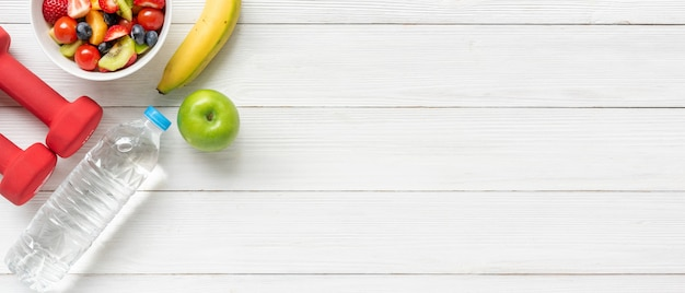 Healthy fruits. fresh fruits salad diet slim fit with dumbbells sport equipment on wooden table background