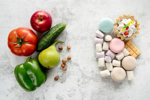 Здоровые фрукты; овощи и фундук на фоне разнообразных десертов