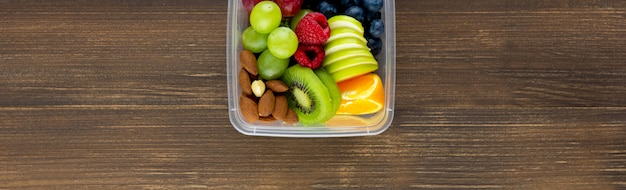 Healthy fruits with almonds in takeaway box on wood banner background