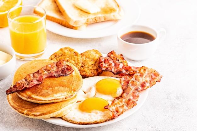 Здоровый полный американский завтрак с оладьями с беконом яиц и латкесами, выборочный фокус.