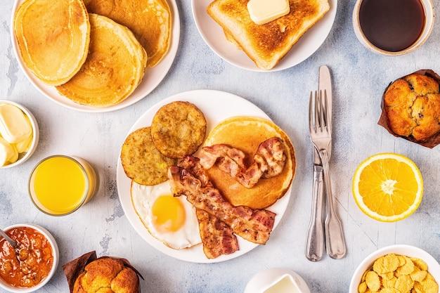 계란 베이컨 팬케이크와 latkes, 평면도가있는 건강식 풀 아메리칸 조식.