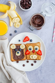 Healthy funny face sandwiches for kids. animal faces toast with peanut and hazelnut chocolate butter, banana, strawberry and blueberry on a white plate with orange juice.
