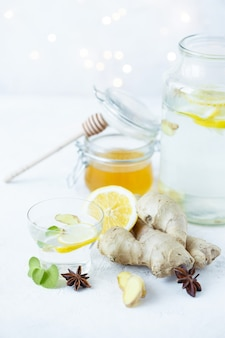 Healthy ginger drink in a cup. ginger root, honey in a jar, lemon on a white table.