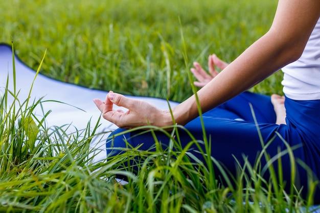 Здоровая девушка занимается йогой на природе в парке летом, сидя в позе лотоса