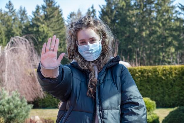 Здоровая девушка в медицинской защитной маске, показывая жест остановки.