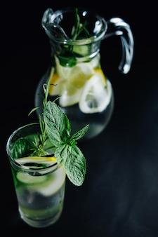 暗い背景の上に石工の瓶にレモン、ミント、ローズマリー、キュウリと健康的なガラスデトックス炭酸水