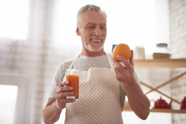 Healthy grandfather got orange juice in glass.