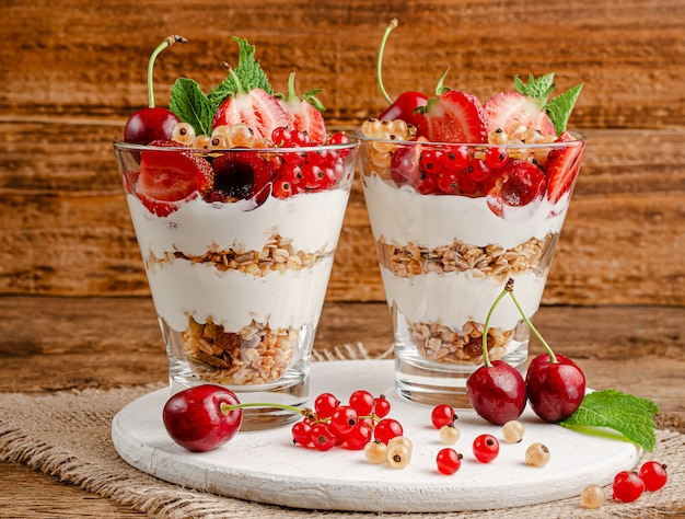 Здоровая мюсли со свежими ягодами и йогуртом на деревянном деревенском пространстве.