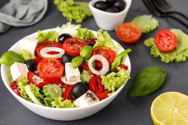 Healthy greek salad of green lettuce, cherry tomato, onion, pepper, feta cheese, black olives, basil, cucumbers, with olive oil and lemon juice, closeup, horizontal orientation