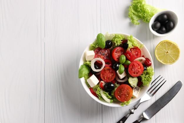 チェリートマト、タマネギ、コショウ、フェタチーズ、ブラックオリーブ、バジル、きゅうりのヘルシーなギリシャ風サラダ、白い背景にオリーブオイルとレモンジュース