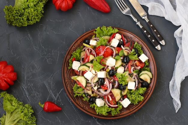 Здоровый греческий салат из салата, помидоров, сыра на тарелке на темном фоне