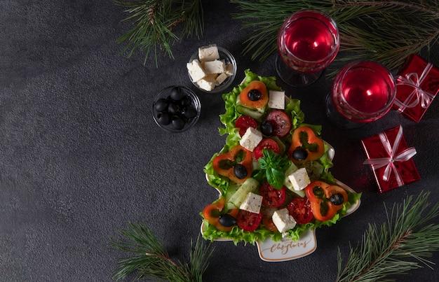 건강한 그리스 샐러드는 축제 장식과 어두운 배경에 와인 두 잔을 곁들인 크리스마스 트리로 접시에 제공됩니다. 복사 공간