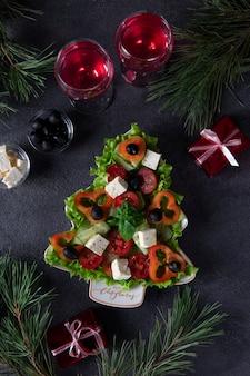 건강한 그리스 샐러드는 축제 장식과 어두운 배경에 와인 두 잔을 곁들인 크리스마스 트리로 접시에 제공됩니다. 세로 형식. 평면도