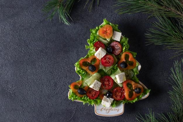 건강한 그리스 샐러드는 어두운 배경에 축제 장식이 있는 크리스마스 트리로 접시에 제공됩니다. 위에서 볼. 복사 공간