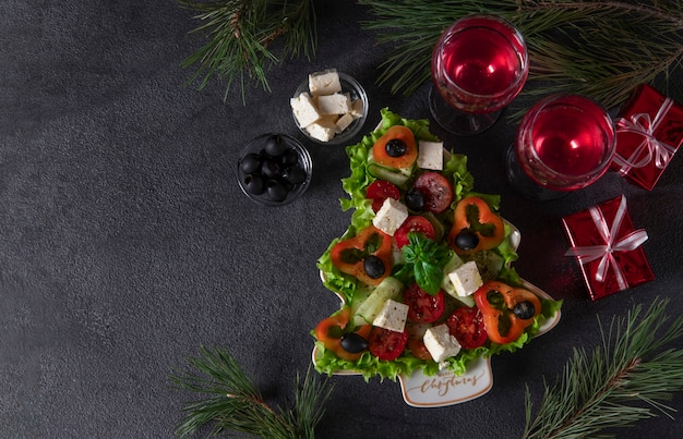 Healthy greek salad served in plate as christmas tree with festive decoration and two glasses of wine on dark background. copy space