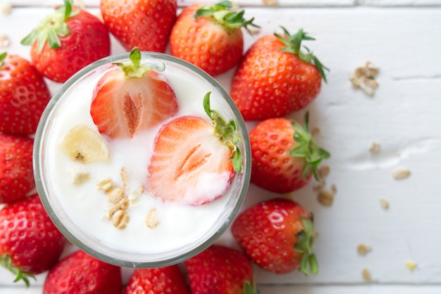 Healthy greek yogurt with strawberries and muesli in the glass on a old wooden table.