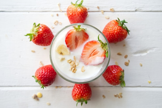 Healthy greek yogurt with strawberries and muesli in the glass on a old wooden with table.