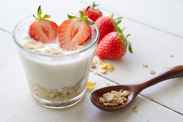 Healthy greek yogurt with strawberry and muesli in the glass on a old wooden table from side view.