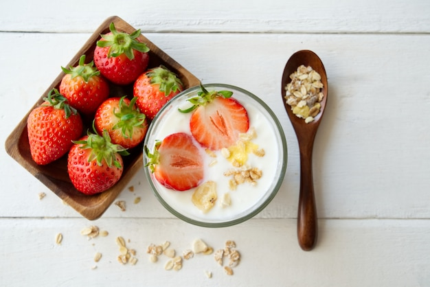 Healthy greek yogurt with strawberry and muesli in the glass on a old wooden with table.