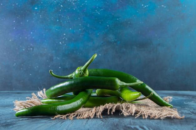 Peperoncini verdi sani disposti su fondo blu.