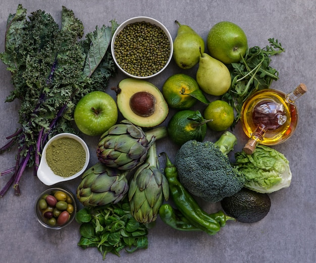 Healthy green food selection for vegetarians: avocado, apples, broccoli, artichokes, tangerines, mung beans, lettuce, olives, rucola, kale, matcha tea, pears