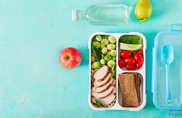 Healthy green meal prep containers with  vegetables and fruits