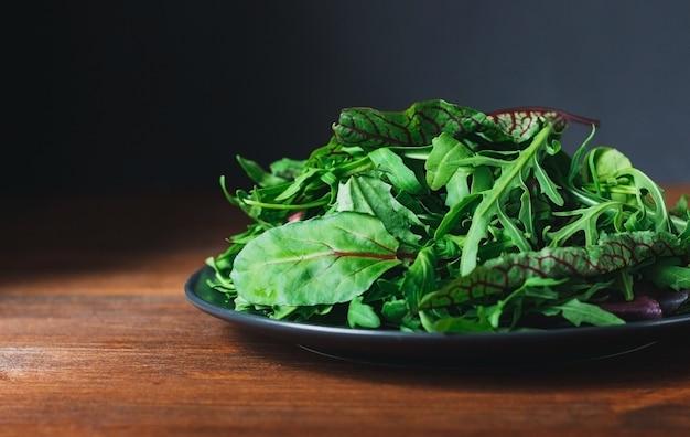 Листья салата здорового зеленого микса на тарелке на деревянном столе
